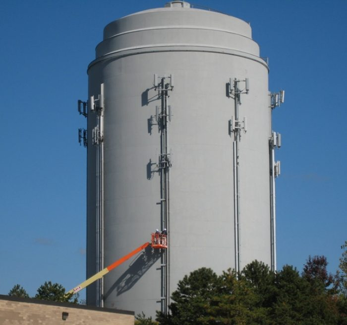Field Painting of cellular communications equipment to match tank color utilizing a boom lift.  Industrial Communications Equipment Painting